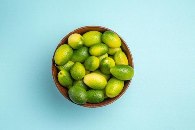 Top close-up weergave fruit groen fruit in kom op het blauwe oppervlak