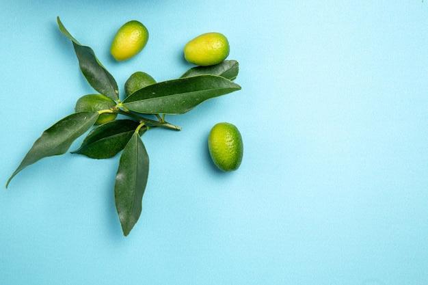 Top close-up weergave fruit groene citrusvruchten met bladeren op de blauwe tafel