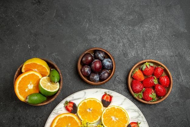 Top close-up weergave fruit op tafel citroen chocolade bedekte aardbeien en sinaasappel in witte plaat naast bessen en citrusvruchten in kommen op het donkere oppervlak