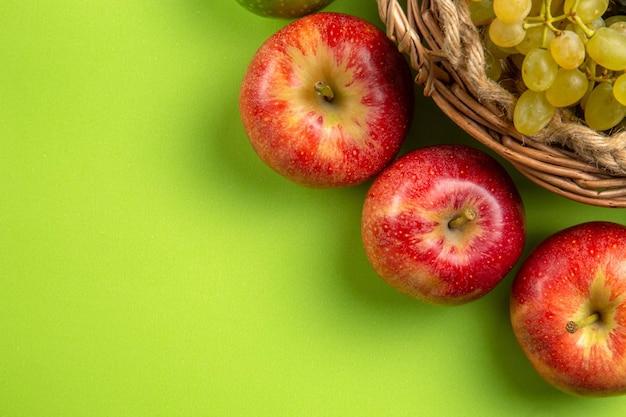 Top close-up weergave fruitmand van groene druiven drie rode appels op de groene achtergrond