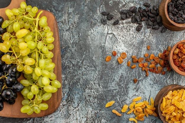 Top close-up weergave gedroogde vruchten kleurrijke gedroogde vruchten de smakelijke druiven op de snijplank