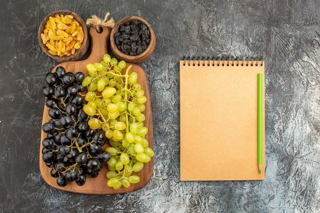 Top close-up weergave gedroogde vruchten notebook potlood druiven op het houten bord twee kommen gedroogd fruit