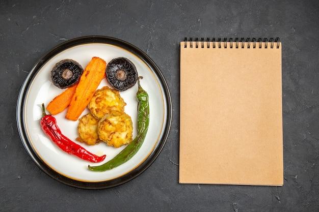 Top close-up weergave geroosterde groenten plaat van de smakelijke geroosterde groenten crème notebook