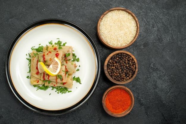 Top close-up weergave gevulde kool gevulde kool met citroen kruiden en saus en kommen rijst kleurrijke kruiden en zwarte peper op zwarte tafel