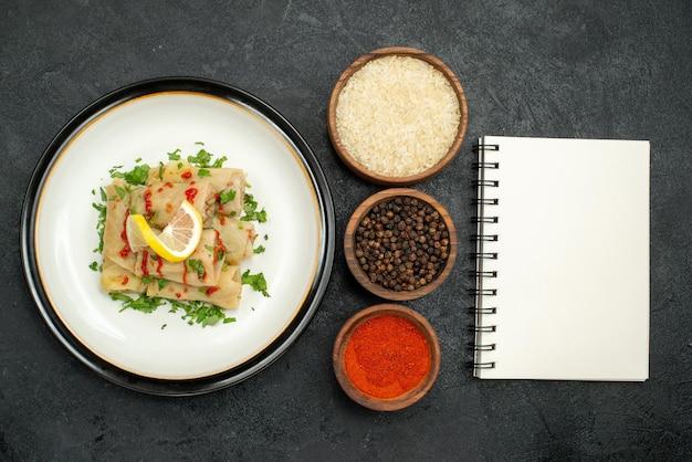 Top close-up weergave gevulde kool gevulde kool met citroenkruiden en saus op witte plaat en kommen rijst kleurrijke kruiden en zwarte peper naast wit notitieboekje op zwarte tafel