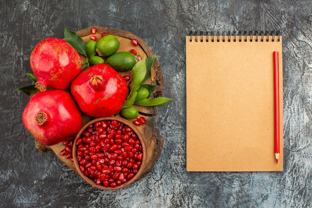 Top close-up weergave granaatappels granaatappels op het houten bord crème notebook rood potlood