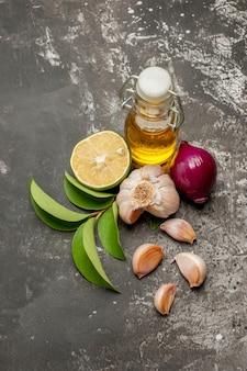 Top close-up weergave kruiden knoflook ui citroen bladeren en fles olie op de donkere tafel