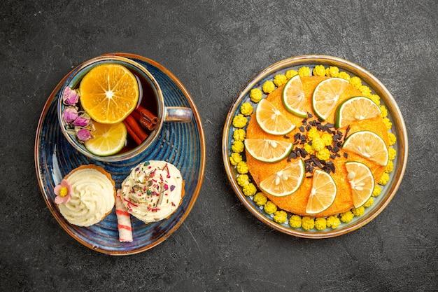 Top close-up weergave kruidenthee een kopje kruidenthee met citroen en twee cupcakes met room naast het bord van een smakelijke cake met limoenen op de zwarte tafel