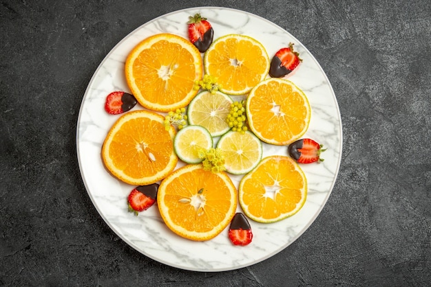 Top close-up weergave oranje gesneden sinaasappel citroen en met chocolade bedekte aardbeien op witte plaat in het midden van de tafel