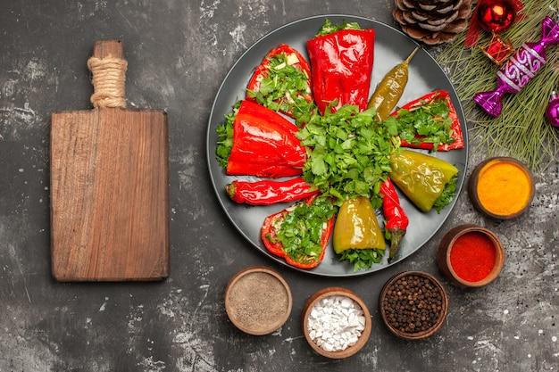 Top close-up weergave paprika's de smakelijke paprika's de snijplank specerijen kerstboom speelgoed
