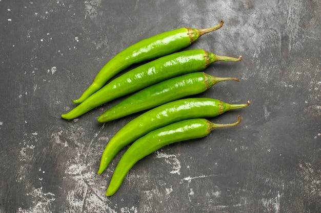 Top close-up weergave paprika's groene hete pepers op de donkere tafel