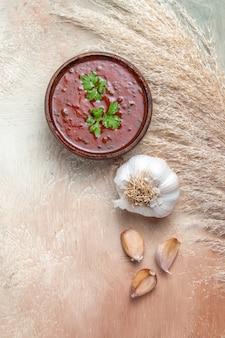 Top close-up weergave saus kan smakelijke saus in kom naast de knoflook