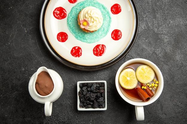 Top close-up weergave smakelijk dessertbord van cupcake met room en sauzen een kopje smakelijke kruidenthee naast de kom chocoladeroom op de donkere tafel