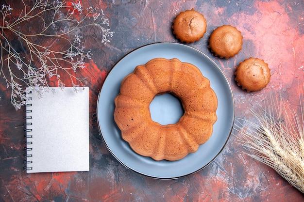Top close-up weergave smakelijke cake smakelijke cake op de blauwe plaat drie cupcakes notebook tarwe oren