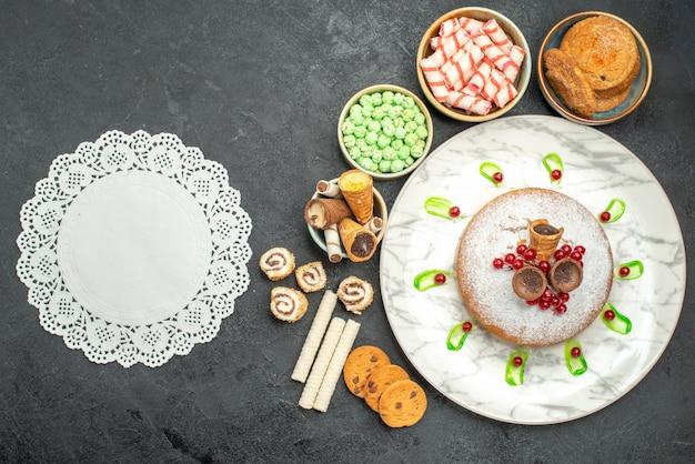 Top close-up weergave snoep een cake met rode aalbessen kleurrijke snoepjes wafels kanten kleedje