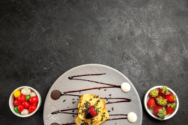 Top close-up weergave snoep grijze plaat van stukjes cake met chocoladesaus en aardbeien naast de kommen met snoep en aardbeien