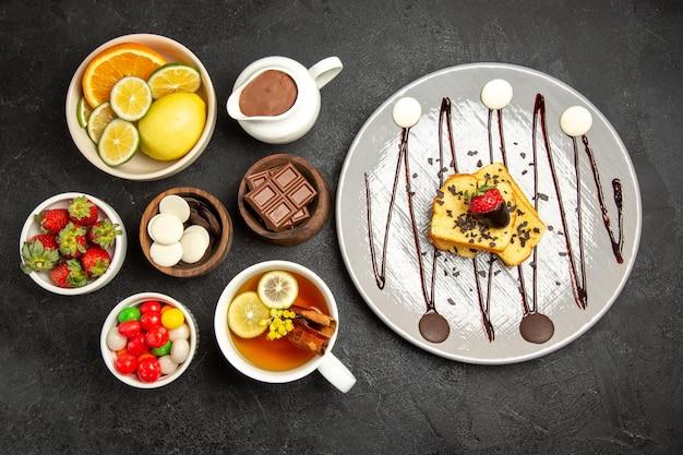 Top close-up weergave snoep in kommen een kopje thee met citroen de kommen van citrusvruchten chocolade snoepjes aardbeien chocolade crème en de plaat van cake