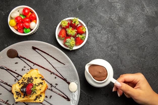 Top close-up weergave snoep kommen van snoep en chocolade crème in de hand naast het bord met stukjes cake met chocoladesaus en aardbeien