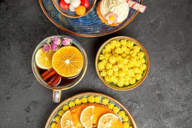 Top close-up weergave snoep op de plaat smakelijke cake met plakjes sinaasappel naast de cupcake met witte room en het kopje thee met kaneelstokjes kom gele snoepjes op tafel