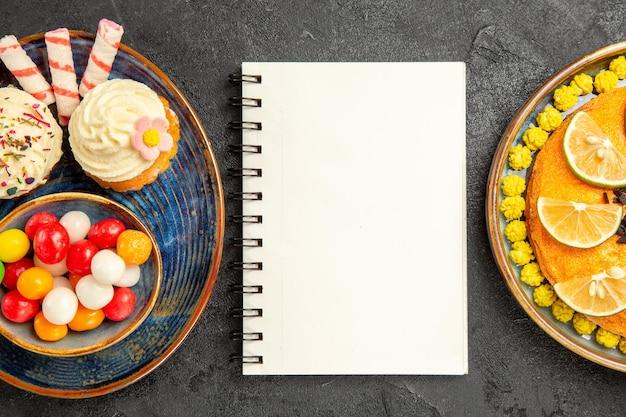Top close-up weergave snoep op de plaat smakelijke cupcakes en kom met snoep naast de witte notebook plaat van cake met plakjes citrusvruchten op de zwarte tafel
