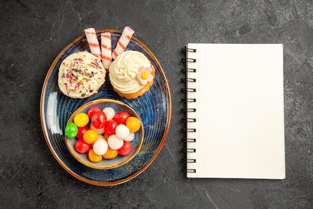 Top close-up weergave snoep op de plaat witte notebook naast de blauwe plaat van de smakelijke cupcakes en kom met kleurrijke snoepjes op de donkere tafel