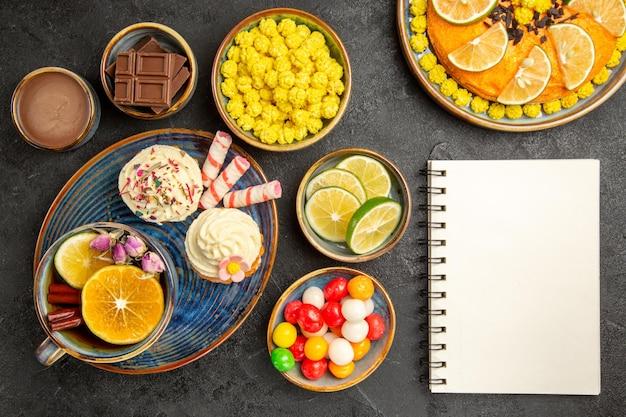 Top close-up weergave snoep op de plaat witte notebook naast de plaat van de smakelijke cupcakes en een kopje thee sinaasappelcake en kommen limoenen chocolade snoepjes en chocolade crème op tafel