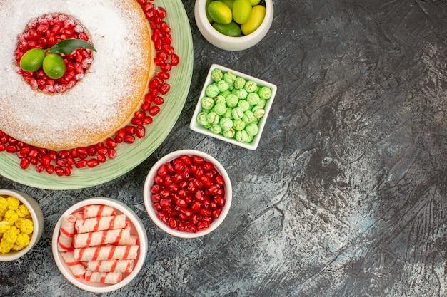 Top close-up weergave snoep smakelijke taart kommen van citrusvruchten kleurrijke snoepjes zaden van granaatappel
