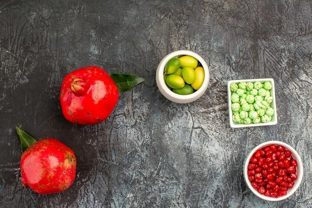 Top close-up weergave snoep twee granaatappel kommen van citrusvruchten granaatappel groene snoepjes