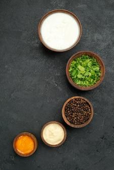 Top close-up weergave specerijen en sauzen kommen van gele en witte sauzen kruiden zwarte peper en zure room in het midden van zwart oppervlak