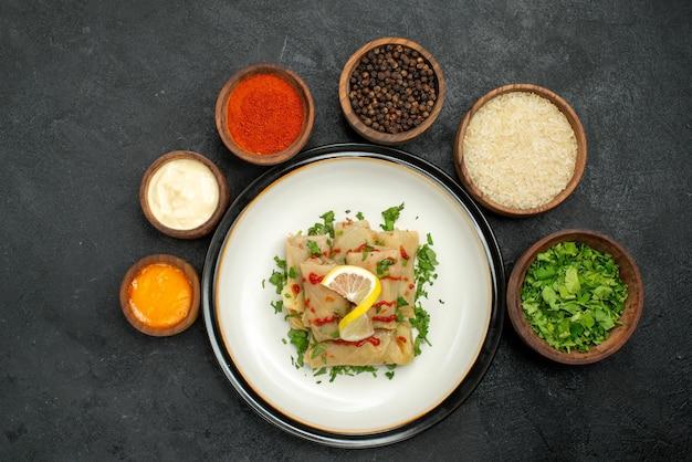 Top close-up weergave specerijen en sauzen kommen van gele en witte sauzen zure room zwarte peper en kruiden rond witte plaat van gevulde kool op donkere ondergrond