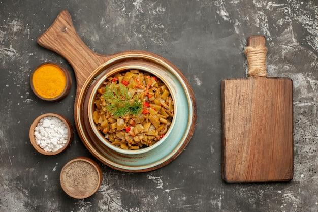 Top close-up weergave sperziebonen met tomaten snijplank naast het bord met bord sperziebonen en drie kruiden