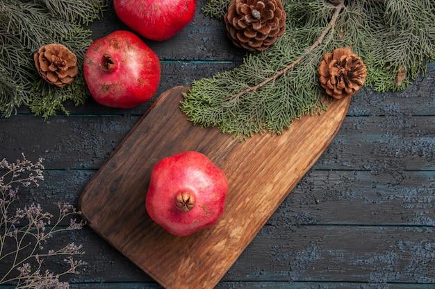 Top close-up weergave takken en granaatappels smakelijke granaatappel op keukenbord naast twee granaatappels en vuren takken met kegels op grijze tafel