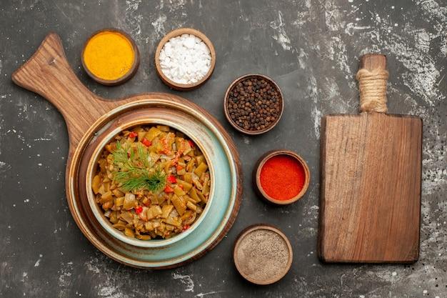 Top close-up weergave tomaten en sperziebonen houten snijplank kom bonen met tomaten naast de vijf soorten kruiden op de zwarte tafel