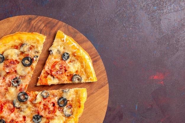 Top close view champignonpizza gesneden gekookt deeg met kaas en olijven op donkere ondergrond pizza eten italiaans maaltijddeeg