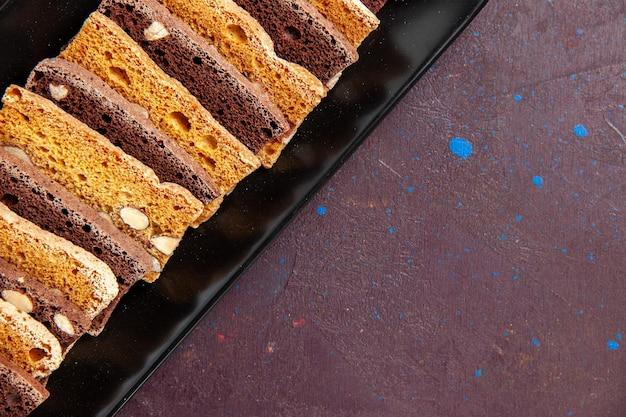Top close view heerlijke gesneden cake met noten in taartvorm op donkere ruimte