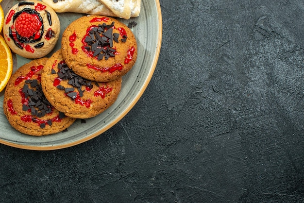 Top close view lekkere koekjes met fruitige gebakjes en stukjes sinaasappel op donkere oppervlakte fruit zoete cake taart thee suiker