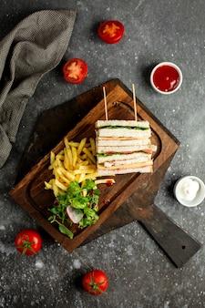 Top club sandwich met groenten frietjes en sauzen op houten breed