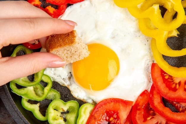Top dichterbij bekijken smakelijke omelet met tomaten en gesneden paprika op donkere ondergrond
