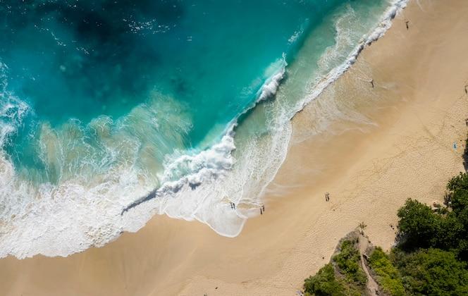 Top down drone shot van het strand van big waves kelingking in nusa penida, bali - indonesië