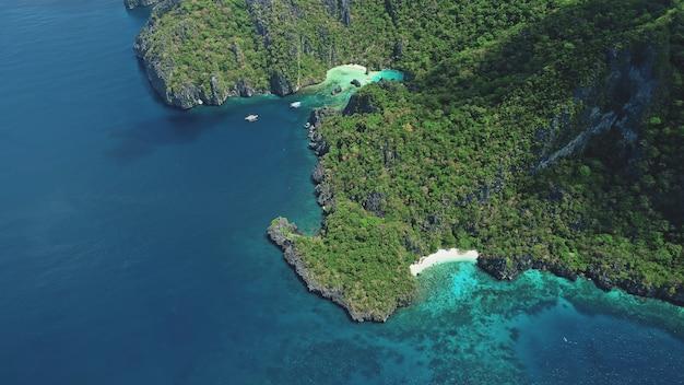 Top-down groen bergachtig eiland in ocean bay in luchtfoto
