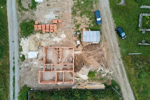Top-down luchtfoto van bouwwerken van nieuwe huis betonnen fundering op bouwplaats.