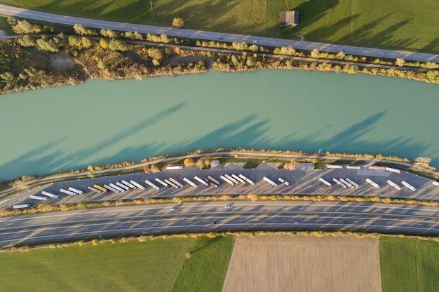 Top-down luchtfoto van de snelweg interstate road met snel bewegend verkeer en parkeerplaats met geparkeerde vrachtwagens.