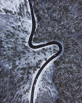 Top-down luchtfoto van een kronkelende weg in het midden van bomen en sneeuw