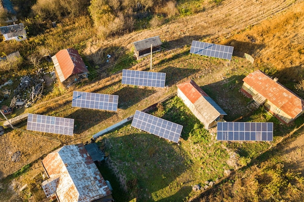 Top-down luchtfoto van fotovoltaïsche zonnepanelen in een groen landelijk gebied.