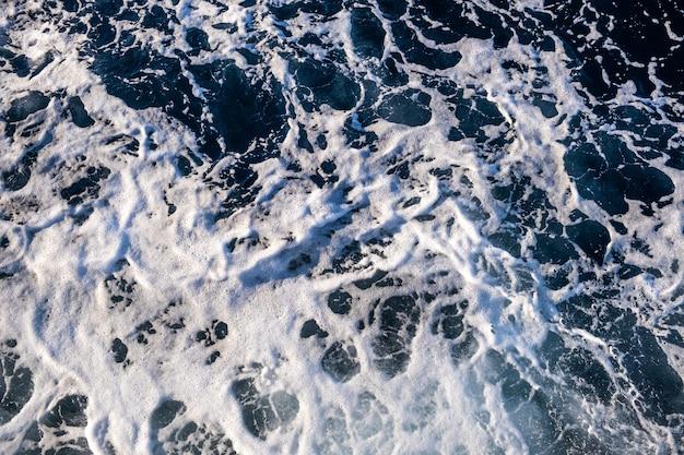 Top-down luchtfoto van het zeewateroppervlak. de witte textuur van schuimgolven als natuurlijke achtergrond.