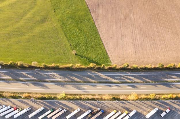Top-down luchtfoto van snelweg interstate weg met snel bewegend verkeer en parkeerplaats met geparkeerde vrachtwagens.