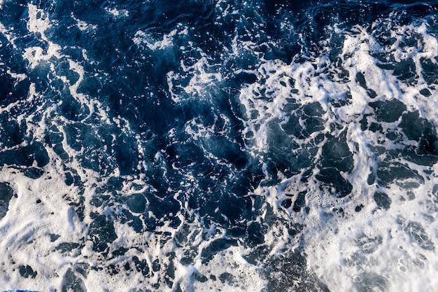 Top-down luchtfoto van zeewateroppervlak. de witte textuur van schuimgolven als natuurlijke achtergrond.