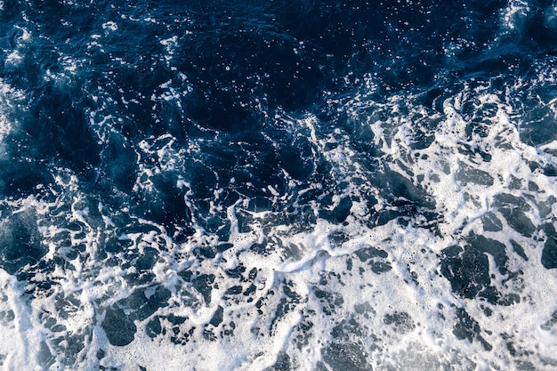 Top-down luchtfoto van zeewateroppervlak. de witte textuur van schuimgolven zo natuurlijk