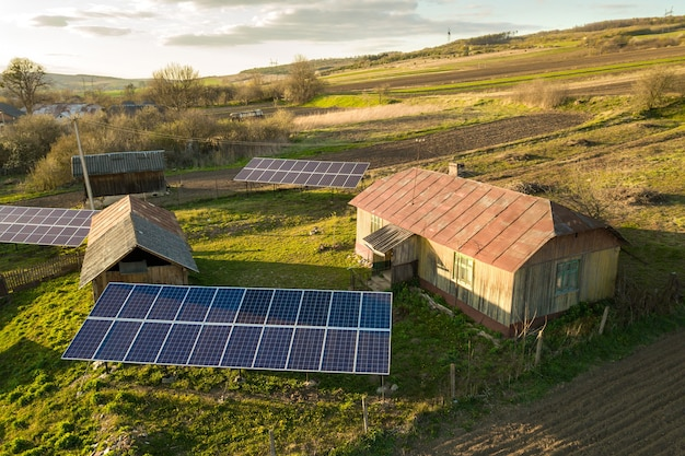 Top-down luchtfoto van zonnepanelen in groene landelijke dorpswerf.