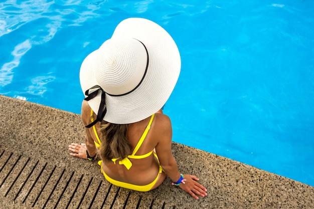Top down mening van jonge vrouw die gele strohoed dragen die dichtbij zwembad met duidelijk blauw water rusten op de zomer zonnige dag.